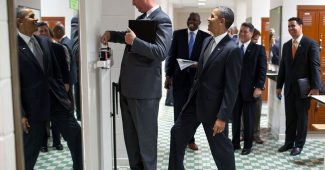 President Obama steps on the scale that trip director Marvin Nicholson is weighing himself on (2010)