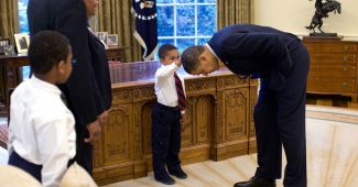 A National Security staffer's son Jacob touches President Obama's hair to see if it felt like his (2009)