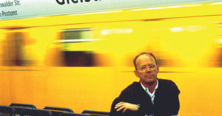 Spiekermann posing at Berlin's Gleisdreieck u-bahn station, the vivid yellow color he chose for the the BVG's post-unification redesign visible on the train in the background.